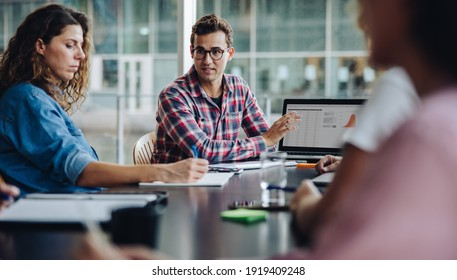 Trainee professional showing his proposal on laptop to team in boardroom. Businessman giving his presentation over laptop to colleagues in office.