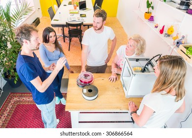 trainees and designers meeting around a 3D printer, discussing novel technologies and new product ideas and developments using 3D printing technology