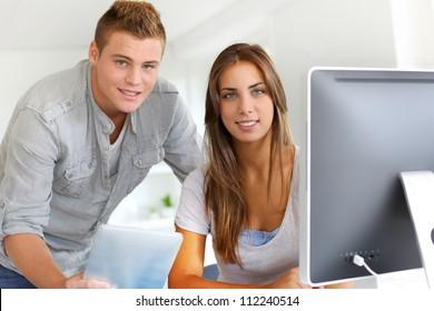 Trainees in office working on desktop computer