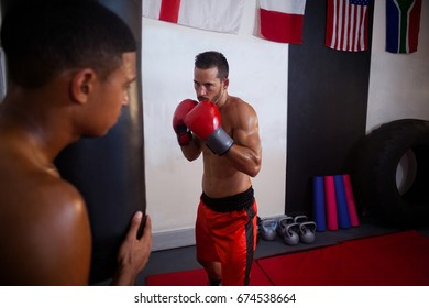 Trainer assisting man in boxing at fitness studio