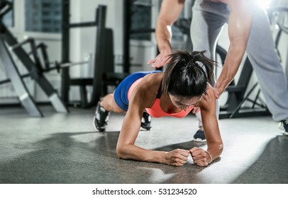 Trainer assisting a muscular woman on a plank position.
