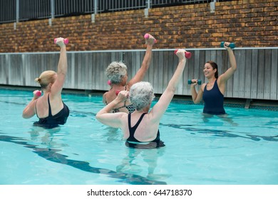 Trainer assisting senior women in weightlifting in swimming pool