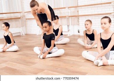 The trainer of the ballet school helps young ballerinas perform different choreographic exercises. They rehearse in the ballet class. The teacher communicates with the children.