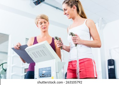 Trainer with body fat scale in gym measuring woman