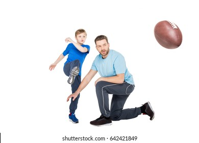 Trainer with child in casual clothes playing football isolated on white
