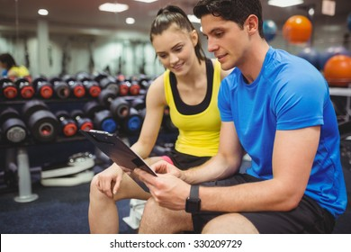 Trainer and client discussing her progress at the gym