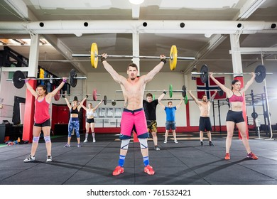 Trainer With Clients Lifting Barbells In Fitness Club