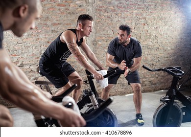 trainer gives support young man on a spinning training