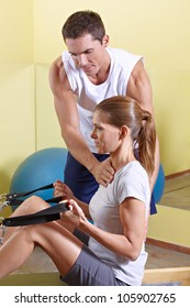 Trainer giving advice to woman in fitness centerat rowing machine