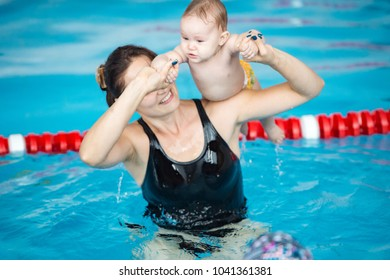 trainer giving son a swimming lesson in pool indoors.