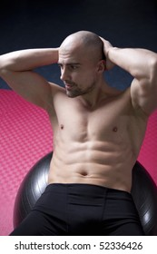 Trainer in the gym, with great muscle sexy body, showing well trained abs, on pilates ball