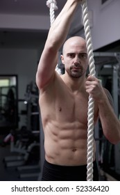 Trainer in the gym, looking at the camera, with great body, showing sexy trained body with muscle, working on rope