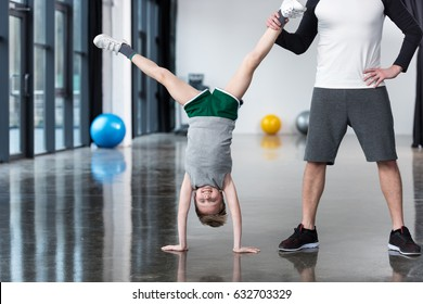 Trainer helping boy standing on hands at exercise room