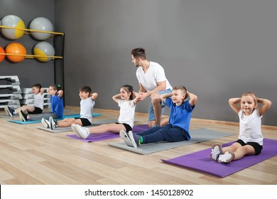 Trainer helping children to do physical exercise in school gym. Healthy lifestyle