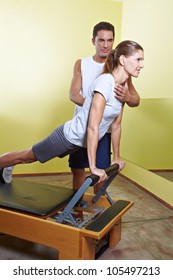 Trainer helping woman with posture correction in fitness center