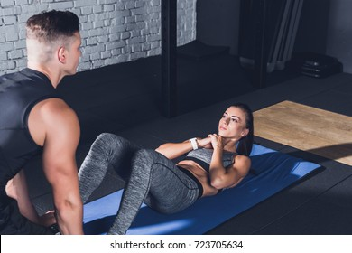 trainer helping young woman to do abs exercises on mat in gym