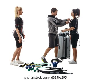 Trainer helps fitness women to set full electrical muscular stimulation suits. Various sport gear like kettlebells, dumbbells, belts and expanders around them. Isolated on white background.