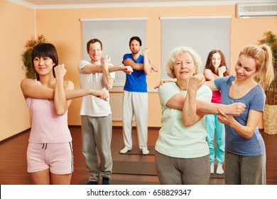 Trainer helps senior woman with yoga exercise at a fitness center