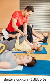 Trainer helps woman with stretching exercise during rehab course