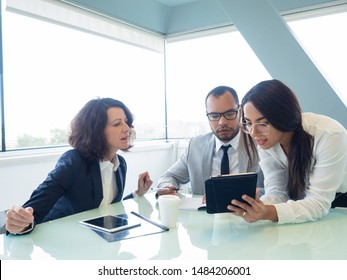 Trainer instructing interns about ongoing projects. Young business woman showing tablet screen to male and female colleagues in meeting room. Mentorship concept