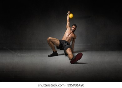 trainer lying down with kettlebell on hand, dark background