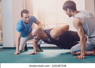 Trainer shows correctness of pushups on one hand. Two men are watching a trainer who does push ups on one arm. The effectiveness of exercises on the strength of the hands and back. Fitness training