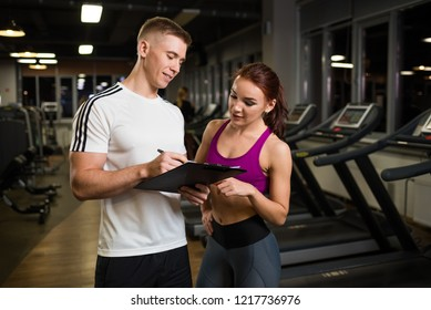 The trainer with a smile shows records in a clipboard to the client.