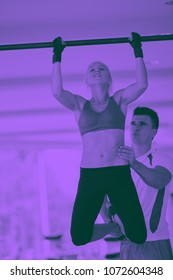 trainer support young woman while lifting on bar in fitness gym indoors duo tone