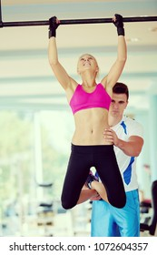 trainer support young woman while lifting on bar in fitness gym indoors