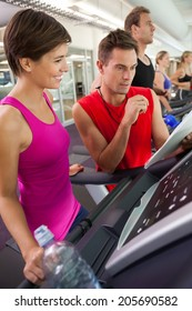 Trainer talking to his client on the treadmill at the gym