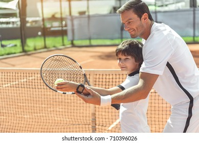 Trainer teaching boy to play tennis