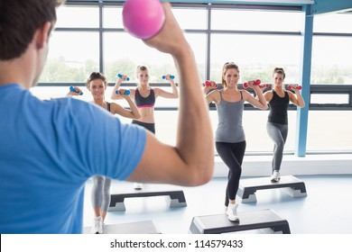 Trainer teaching his aerobics class while lifting weights in gym