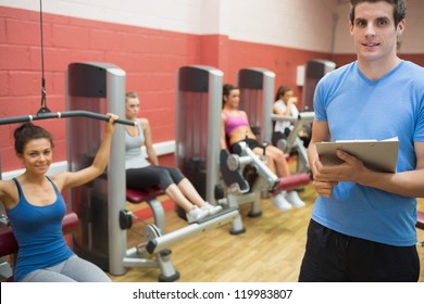 Trainer in weights room with women in gym