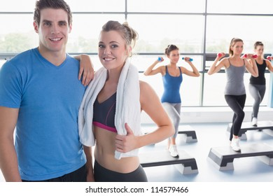 Trainer and woman smiling together while aerobics class taking place in gym