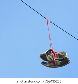 Trainers suspended from power cable over White Post Lane, Hackney Wick, London, UK.