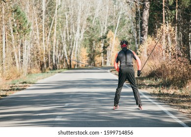 Training an athlete on the roller skaters. Biathlon ride on the roller skis with ski poles, in the helmet. Autumn workout. Roller sport. Adult man riding on skates.