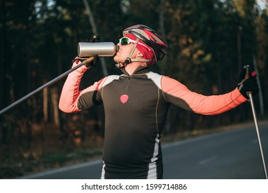 Training an athlete on the roller skaters. Biathlon ride on the roller skis with ski poles, in the helmet. Autumn workout. Roller sport. Adult man riding on skates. Athlete drinks water from flask.