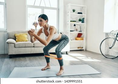 La formation pour devenir le meilleur. Pleine longueur de belle jeune femme en vêtements de sport accroupissant pendant l'exercice à la maison