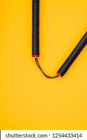Training black nunchaku is isolated on a yellow background.