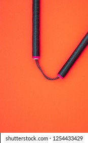 Training black nunchaku is isolated on a red background.