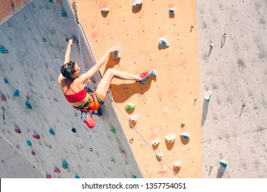 Training at the city climbing gym. A strong woman climbs a climbing route on artificial terrain. Slim girl involved in sports.
