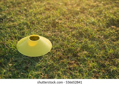 Training cone for football on a green field,  yellow plastic cone on green field.