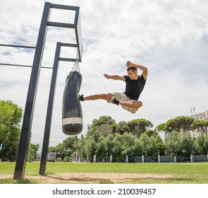 training at the crossfit park, man executes flying kick on the bag