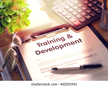 Training & Development- Text on Clipboard with Office Supplies on Desk. Training & Development on Clipboard with Paper Sheet on Table with Office Supplies Around. 3d Rendering. Toned Image.