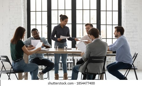 Training handouts. Qualified biracial female mentor trainer giving millennial trainees students paper documents by subject matter to educate, indian woman team leader setting problems to diverse staff