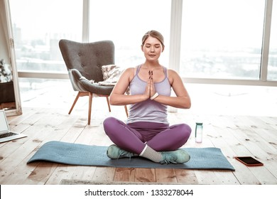 Training at home. Meditative relaxed woman sitting on blue mat in lotus posture and being deep inside her mind