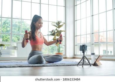 Training zu Hause. Junge asiatische Frau trainieren mit Hantel während Online-Tutorial auf dem Handy.