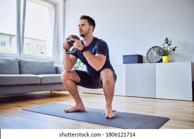 Training at home, young man doing squats with kettlebell weights.