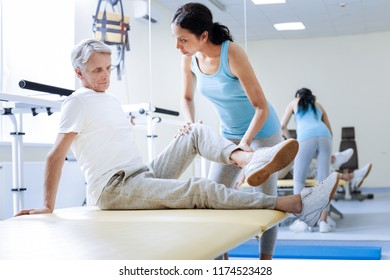 Training muscles. Concentrated medical worker of a progressive modern rehabilitation center bending the injured knee of her tired worried aged patient and looking attentively at him