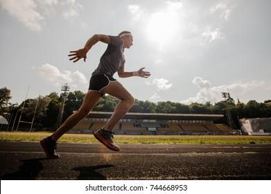 Training. Muscular athlete of the treadmill at the stadium